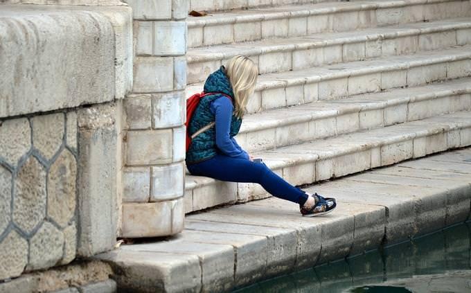 בחן את עצמך בלועזית: נערה עם תיק גב יושבת על מדרגות ברחוב