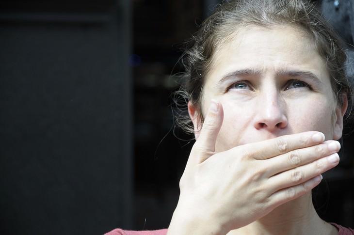 גורמים לטעם מתכתי בפה: אישה ברחוב מכסה את פיה