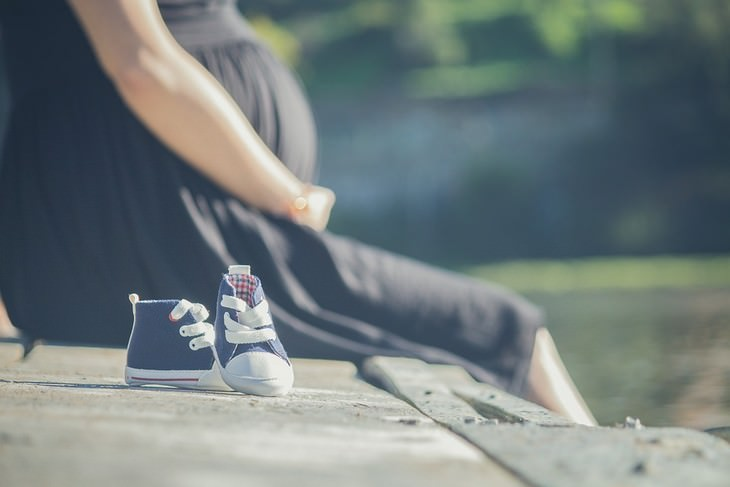 גורמים לטעם מתכתי בפה: אישה בהריון יושבת ליד נעליים של תינוק