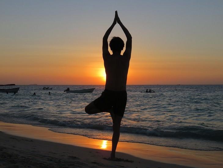 איש עומד בתנוחת יוגה מול שקיעה בים