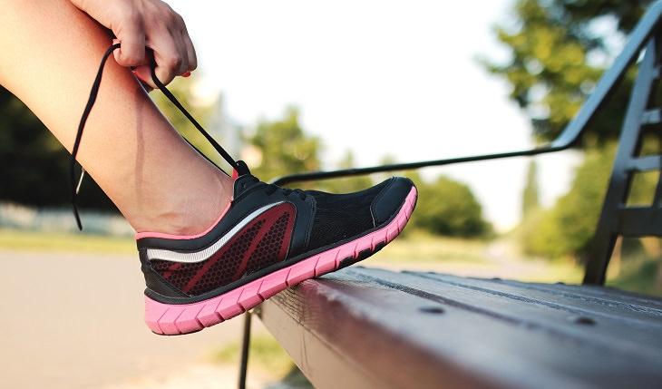 אישה קושרת שרוכים בנעל ספורט על ספסל