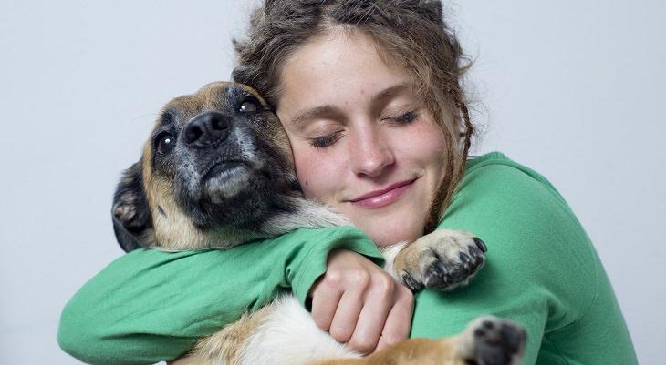 נערה מחבקת כלב