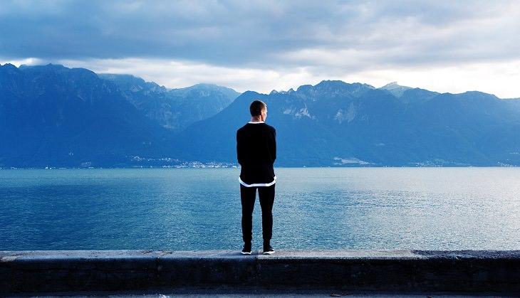 גבר עומד מול נוף הררי ואגם ומביט קדימה