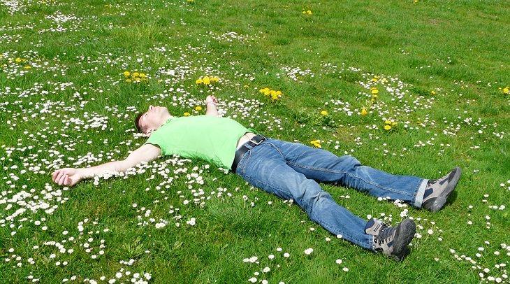 איש שוכב על הדשא עם ידיים לצדדים