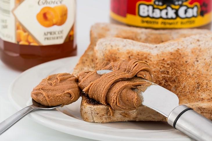 כתמי אוכל נפוצים והדרכים להסירם מבגדים: צנים על צלחת עם סכין שמורחת עליו חמאת בוטנים וכפית עם חמאת בוטנים לצידה
