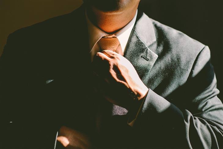 טריקים לשיפור כריזמה: גבר בחליפה מהדק עניבה לצווארו