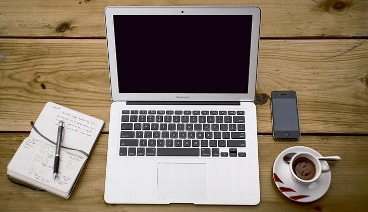 שולחן עבודה עם מחשב נייד, פנקס, כוס קפה וסמארטפון