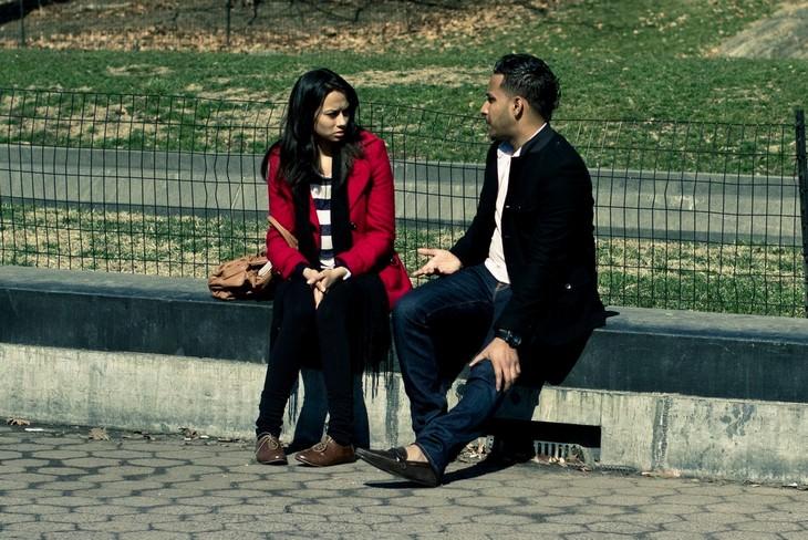 זוג יושב על מעקה בטון ומתווכח