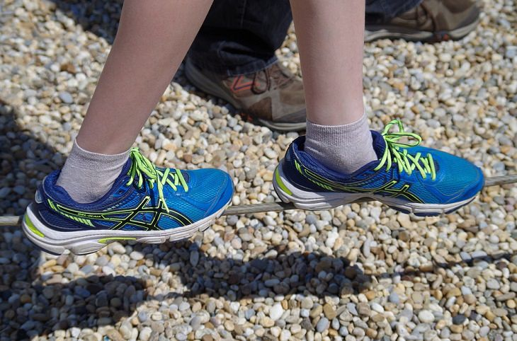 צילום של כפות רגליים עם נעלי ספורט מיוצבות על חבל הליכה