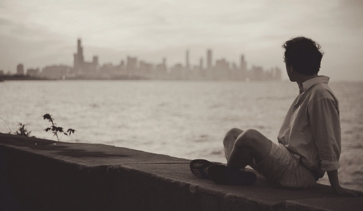 גבר יושב על מזח ומביט בנוף
