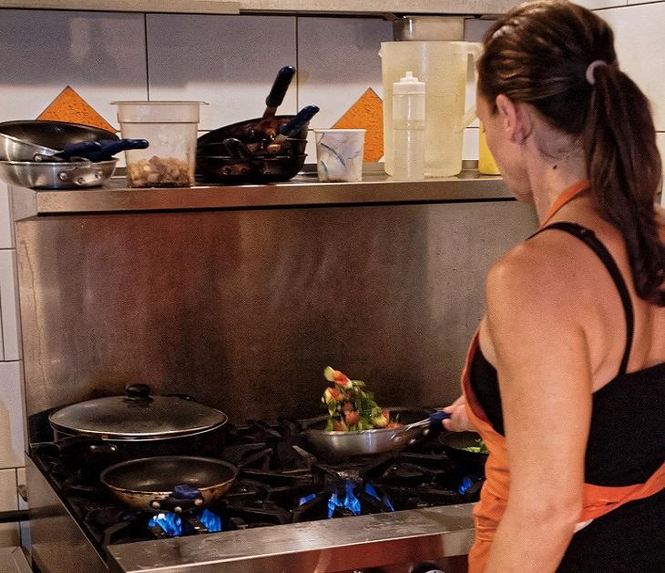 אישה מטגנת ירקות במחבת