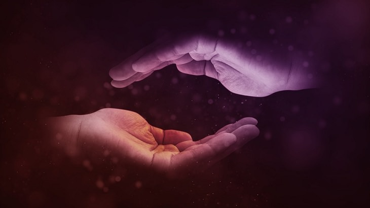 ידיים עוטפות כדור דמיוני, על רקע צבעי סגול