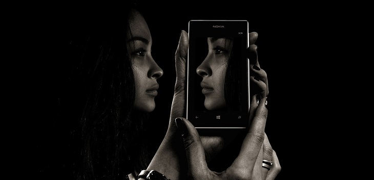 אישה מביטה בפרופיל, ולצידה מסך טלפון חכם עם צילום פניה בפרופיל הפוך