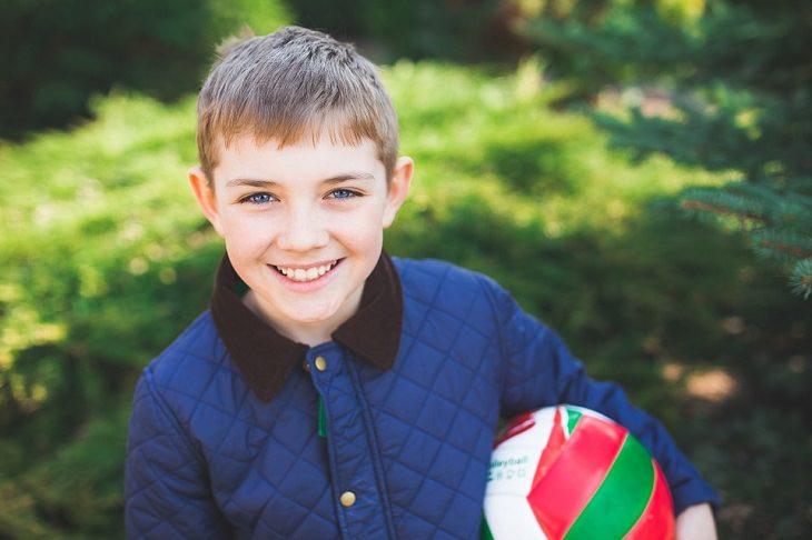 ילד אוחז בכדור ומחייך