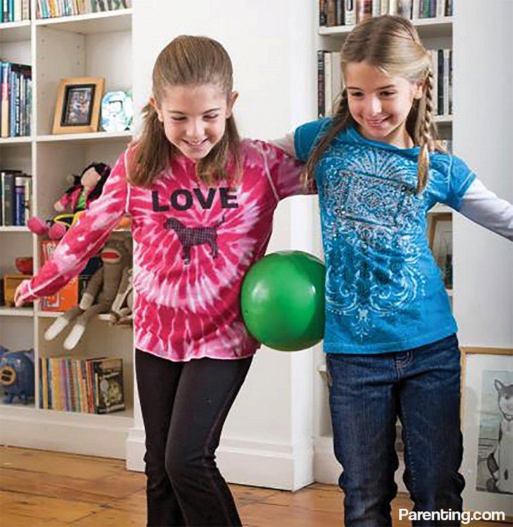 שתי ילדות משחקות עם כדור המונח בין המותניים שלהן
