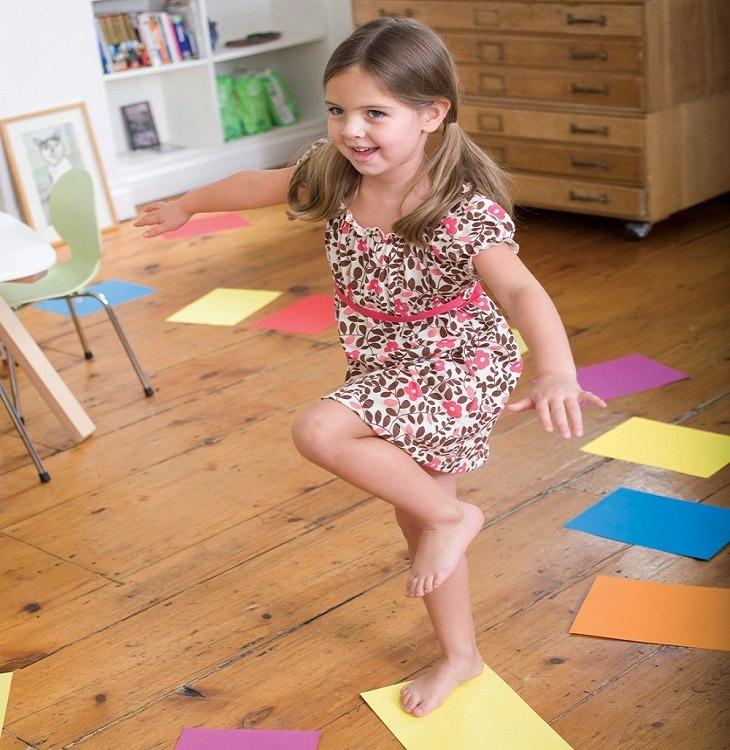 ילדה משחקת בקפיצה בין דפים צבעוניים על הרצפה