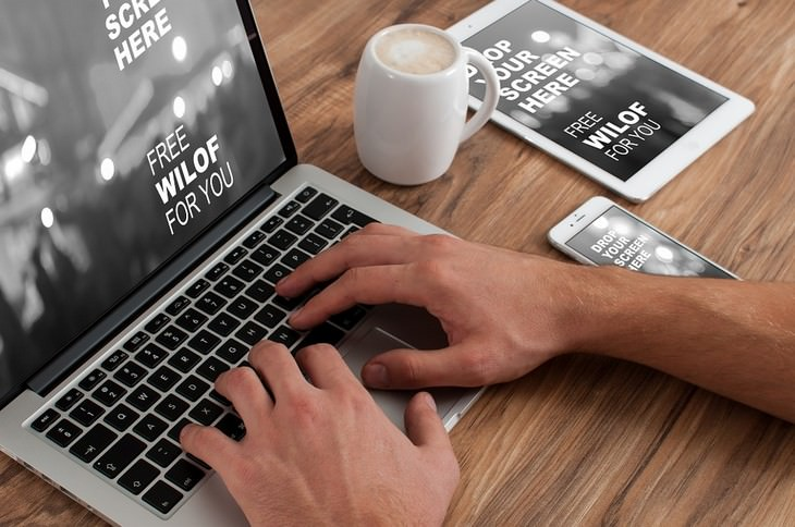 ידיים של גבר על מקלדת של מחשב נייר עם כוס קפה לצידו