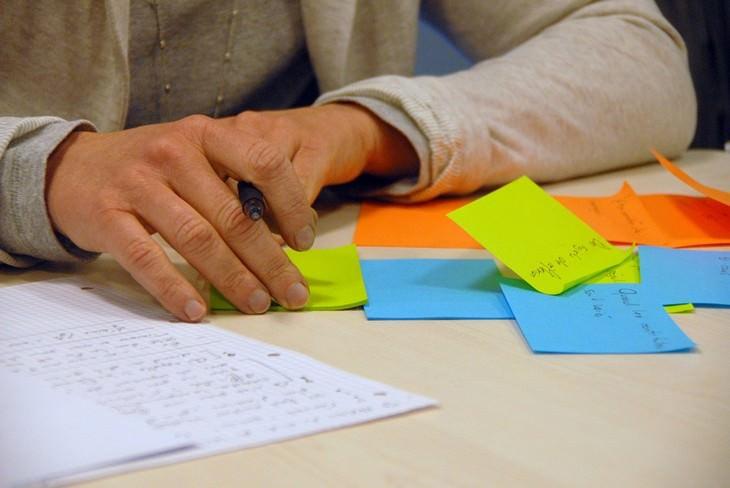 יד של גבר מחזיקה עט מעל שולחן עם פתקיות צבעוניות