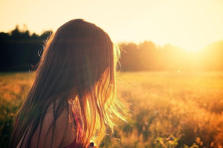 אשה עם שיער ארוך על רקע שדה שמשי
