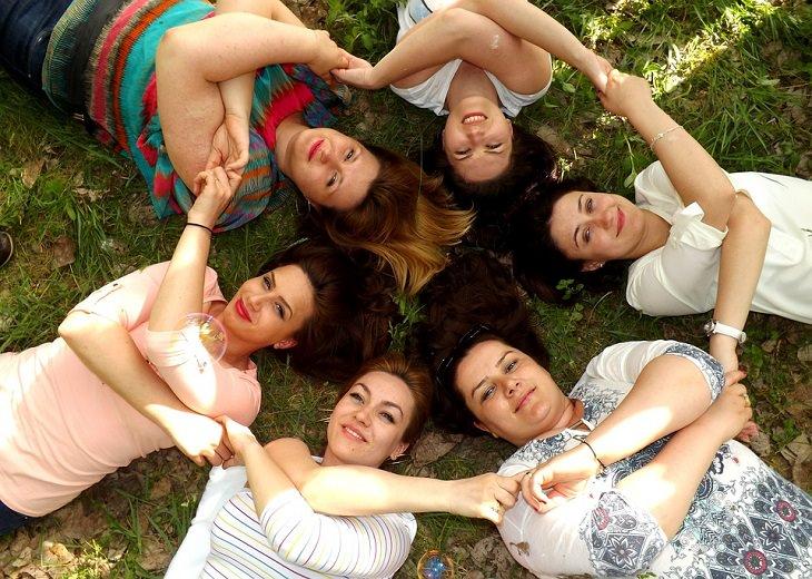 הצעות למשחקי חברה: נשים מחוייכות שוכבות על דשא ואוחזות ידיים