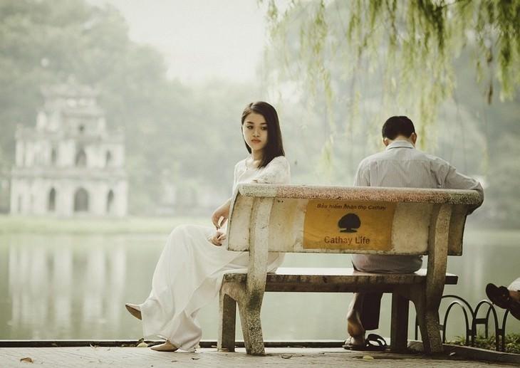 זוג יושב על ספסל בשני קצוות נגדיים