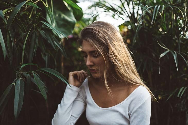 אישה מדוכדכת יושבת בין שיחים