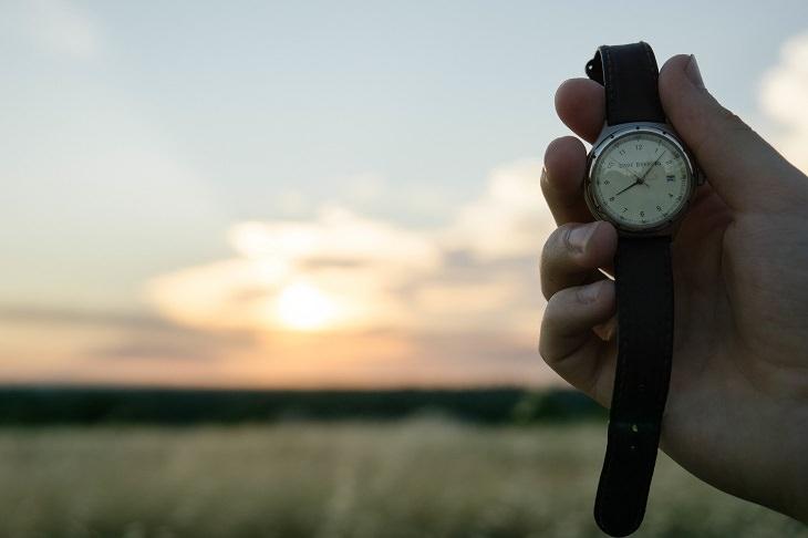 יד אוחזת בשעון על רקע שמש
