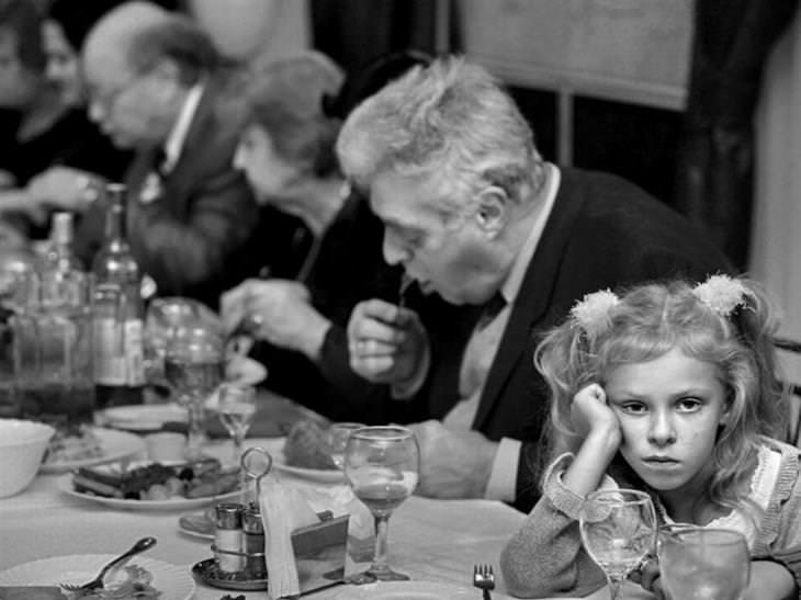 ילדה יושבת מול שולחן סעודה ומסתכלת על המצלמה במבט משועמם