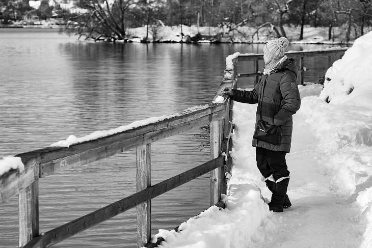 אישה בלבוש חורפי עומדת בשלג מול אגם