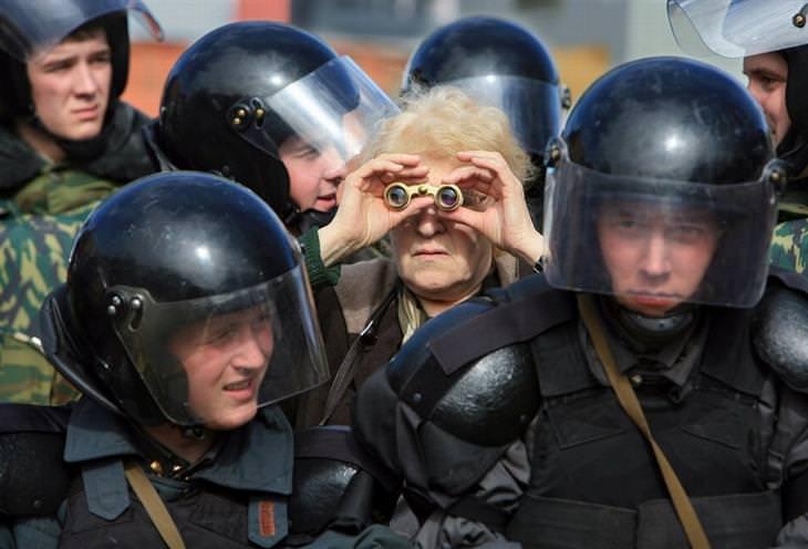 אדם מבוגר מסתכל למרחק בעזרת משקפת בין קבוצת שוטרים בלבוש מגן