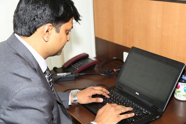 גבר בחליפה יושב כפוף מול מחשב נייד