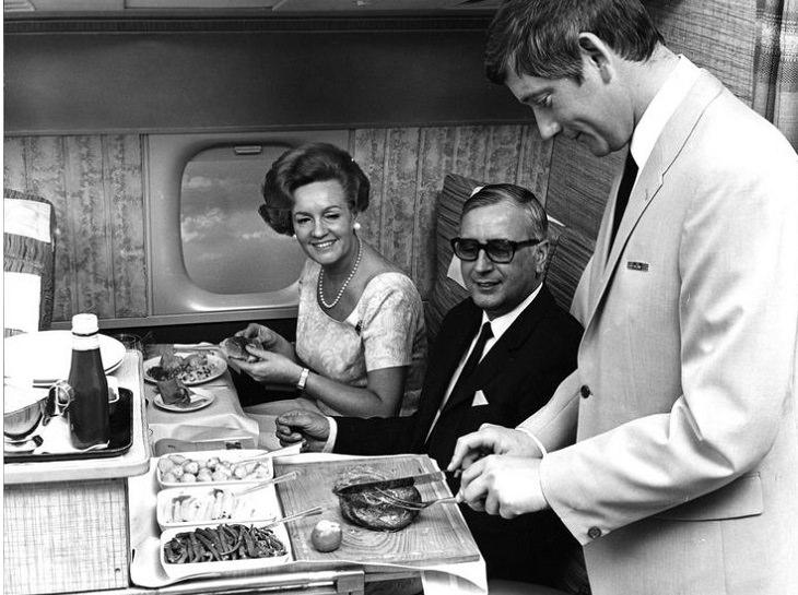 גבר מגיש אוכל לזוג על מטוס