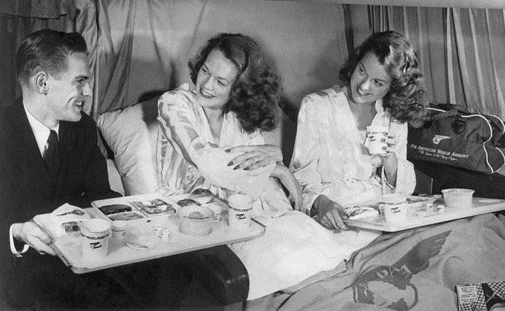 גבר מגיש אוכל לנשים שכובות על כורסאות במטוס