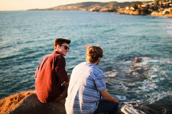 שני חברים מחויכים יושבים על צוק מול הים ומדברים
