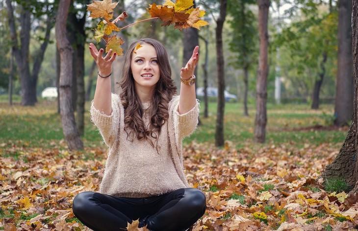 אישה יושבת ביער וזורקת עלים לאוויר