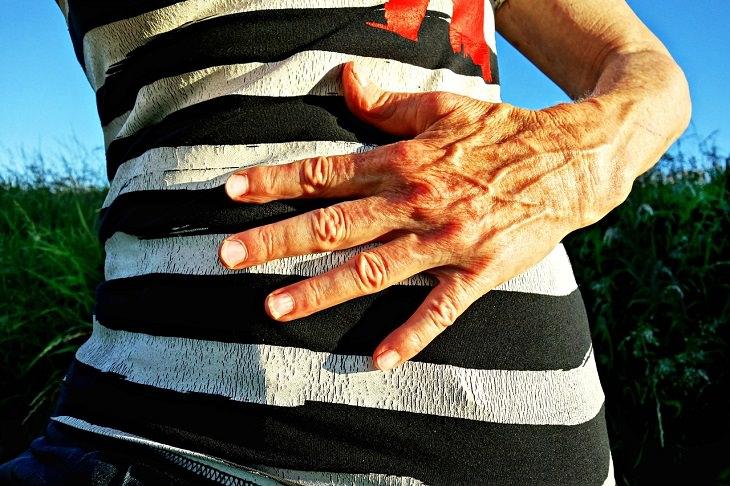 יתרונות רגלת הגינה: ידה של אשה מונחת על בטנה