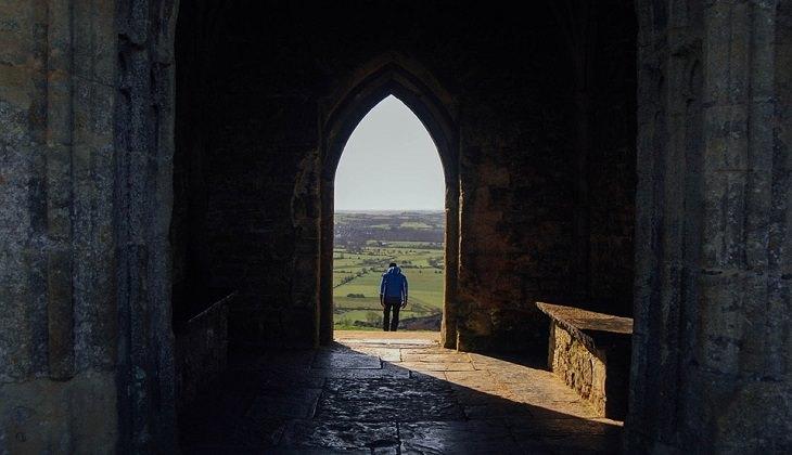 אדם עומד במרחק מעבר לפתח של מבנה
