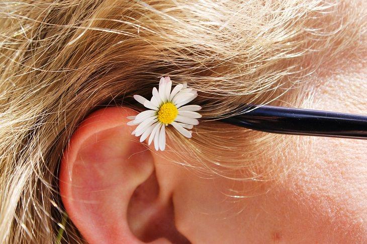 צילום תקריב של אוזן של בחורה בלונדינית, ועליה פרח צהוב