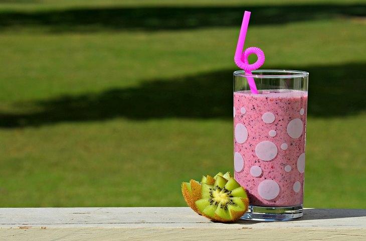 כוס עם מיץ פירות וקיווי בצידה, ברקע דשא