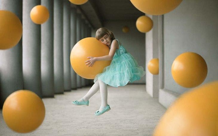 ילדה נשענת על כדורים מעופפים
