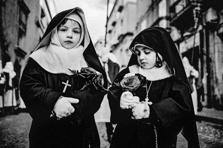ילדות בתלבושת נזירות אוחזות פרחים