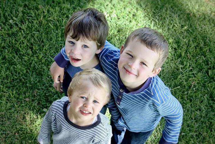 עצות למניעת ריבים בין אחים: שלושה אחים חבוקים מביטים מעלה למצלמה