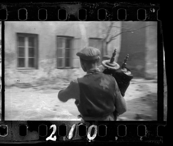 1940: אדם מציל ספר תורה משברי בית הכנסת ברחוב וולבורסקה, שנהרס על ידי הגרמנים
