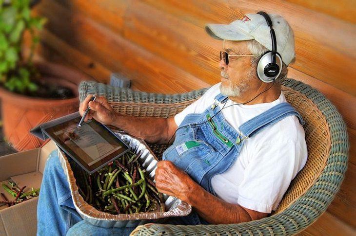 גבר מבוגר יושב במרפסת ומאזין למוסיקה באוזניות