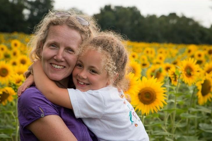 10 דרכים להתמודדות עם ילדים הסובלים מהפרעות קשב וריכוז: ילדה מחבקת אישה בשדה פרחים