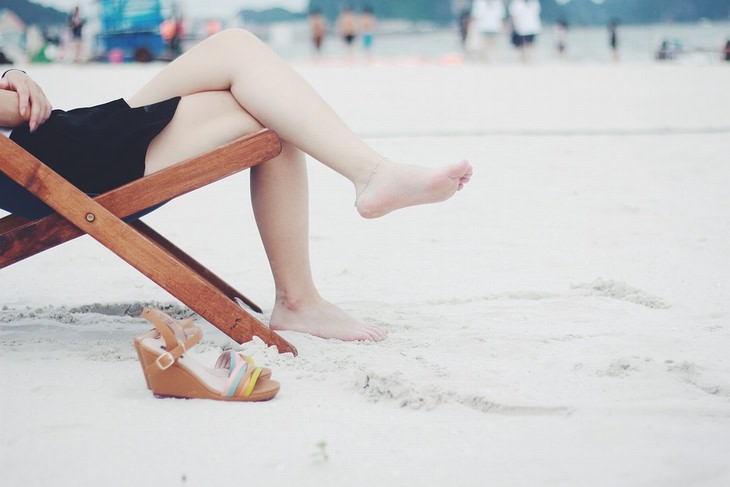 שימושים מפתיעים לקפה: רגלי אישה על כיסא נוח בחוף הים