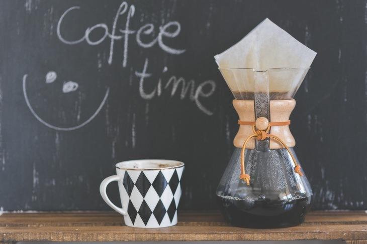 """שימושים מפתיעים לקפה: קנקן קפה מונח ליד כוס, מאחוריהם לוח עם הכיתוב """"זמן לקפה"""" באנגלית"""