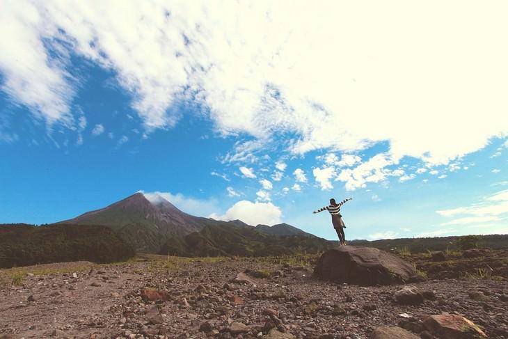 אישה עומדת על סלע מול נוף סלעי ושמיים מעוננים