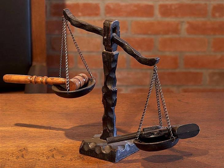 מאזניים עם פטיש של שופט בצד אחד ואקדח בצד השני, שכבד יותר