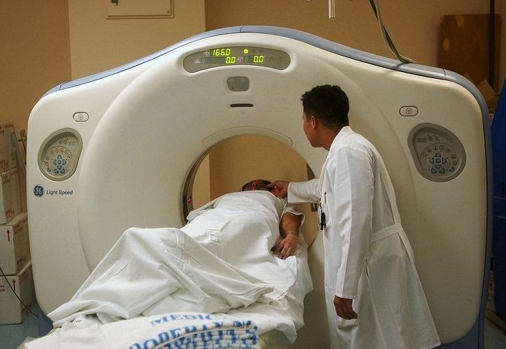 חולה שוכב שעובר בדיקה במכשיר סריקה, איש צוות רפואי מסייע לו